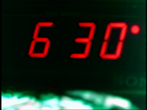OVEREXPOSED close up digital alarm clock / time changing to 6:30 + hand shuts it off