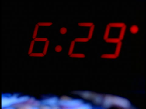 close up digital alarm clock / time changing to 6:30