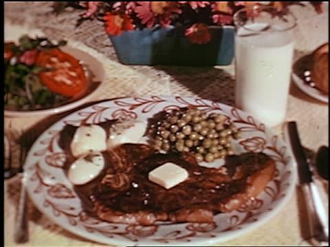 vidéos et rushes de 1948 close up dinner food on plates on table: steak, potatoes, peas, salad + glass of milk / industrial - viande