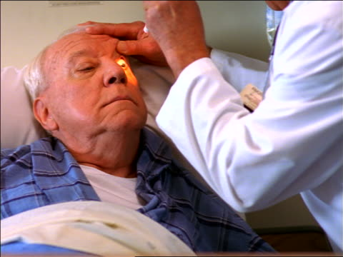 close up doctor checking eyes of senior man in hospital bed