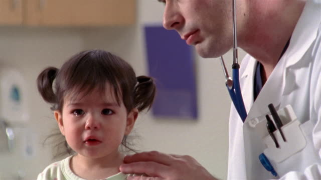 Close up doctor examining crying toddler with stethoscope / zoom out medium shot mother looking at toddler / El Paso, Texas
