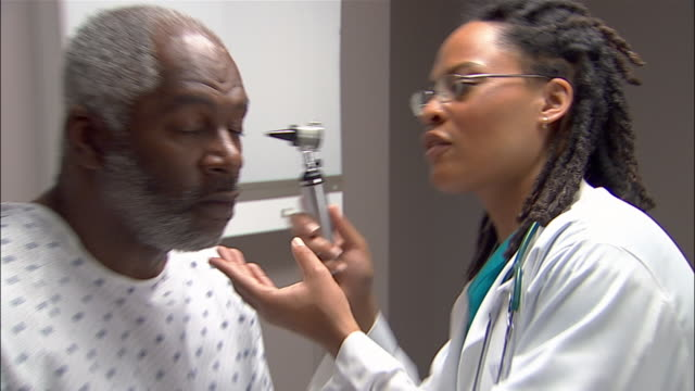 Close up doctor examining patient's ear with otoscope