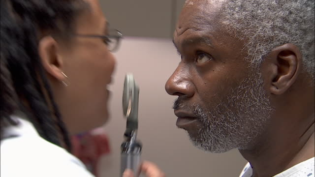 Close up doctor examining patient's eye with opthalmoscope / giving him a lollipop