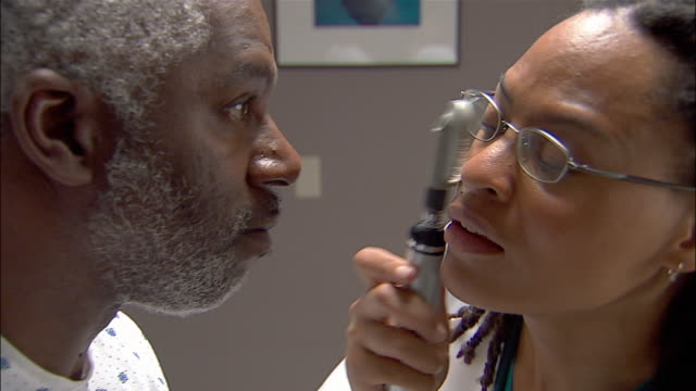 Close up doctor examining patient's eye with opthalmoscope