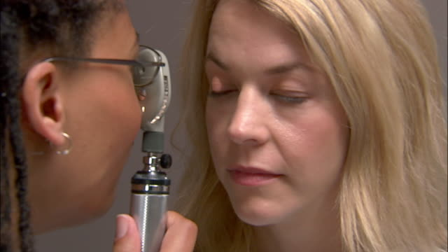 Close up doctor examining patient's eyes with opthalmoscope / writing results on chart