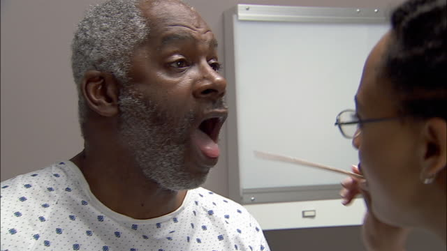 Close up doctor examining patient's mouth / using a tongue depressor
