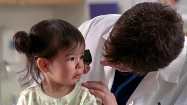 Close up doctor examining toddler's ears with scope / El Paso, Texas