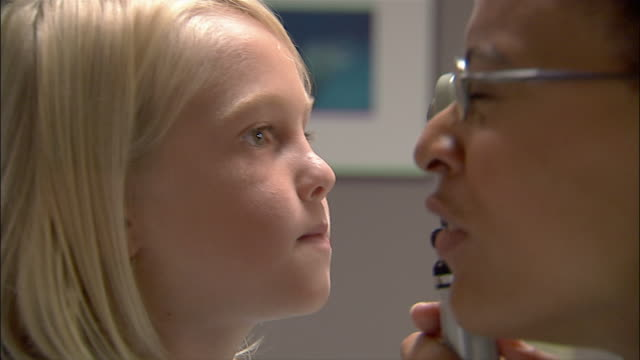 Close up doctor examining young boy's eyes with opthalmoscope