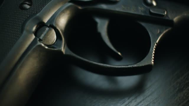 vidéos et rushes de close up dolly across grip, trigger and barrel of pistol on dark background - armement