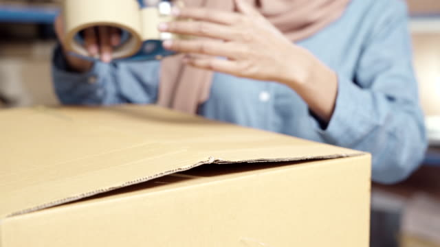 4k uhd close up dolly left : islam muslim female asian warehouse worker packing parcel in warehouse distribution center. using in business warehouse logistic concept. - oregon coast stock videos & royalty-free footage
