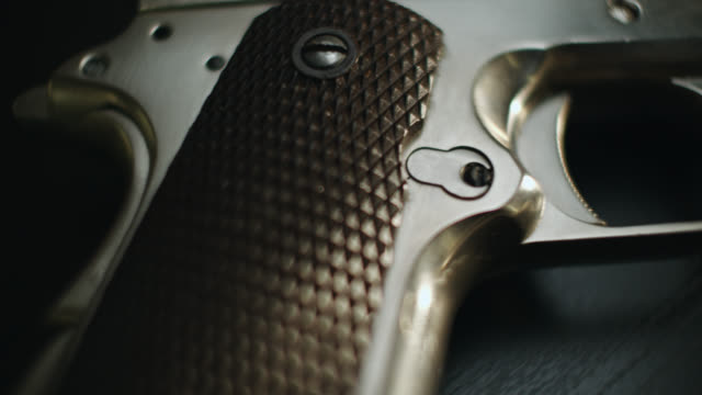 close up dolly shot across grip and barrel of pistol - handgun stock videos & royalty-free footage