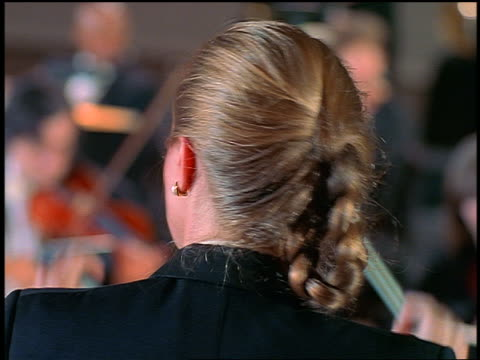 close up dolly shot behind female conductor of orchestra playing / string section in front of her - conductor stock videos & royalty-free footage