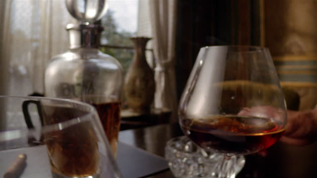 close up dolly shot brandy being poured into snifter in foreground / hand putting cigar on ashtray and lifting snifter in background - sigaro video stock e b–roll