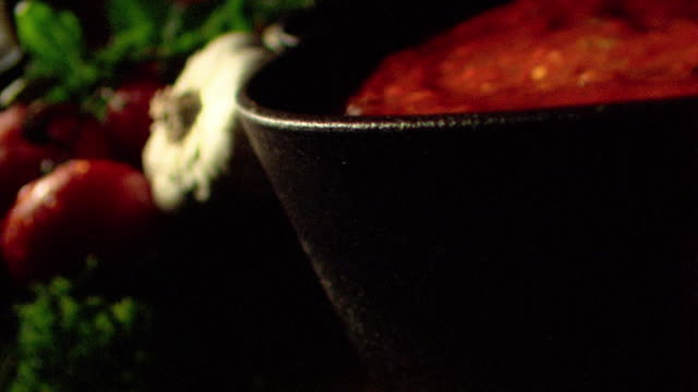 vídeos y material grabado en eventos de stock de close up dolly shot chopped parsley falling into pot of tomato sauce - sauce