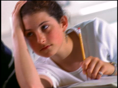 close up dolly shot female high school student with head in hand holding pencil in classroom - solo adolescenti femmine video stock e b–roll