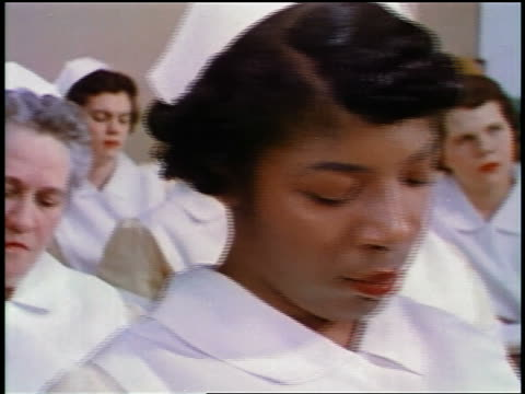 1957 close up dolly shot female nurses of mixed ethnicity sitting at desks looking down + at something offscreen - medical student stock videos and b-roll footage