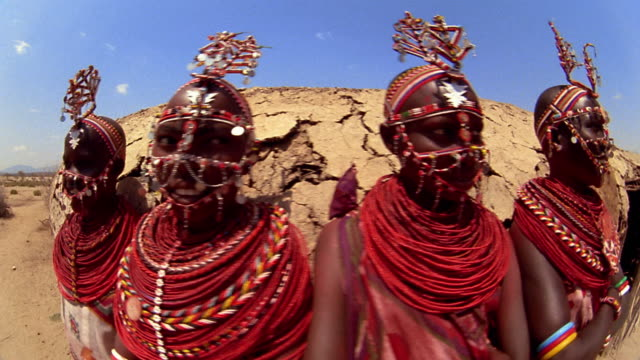 close up dolly shot four young masai tribeswomen standing in front of hut / kenya - masai stock videos and b-roll footage