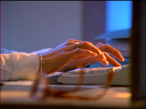 vídeos de stock, filmes e b-roll de close up dolly shot hands of woman sitting at desk typing on computer keyboard - 1990