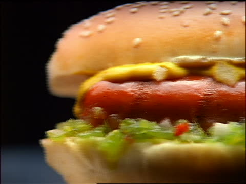 close up dolly shot hot dog with condiments - condiments stock videos and b-roll footage