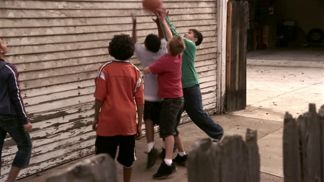 close up dolly shot kids playing basketball in driveway near garage - sporting term stock videos and b-roll footage