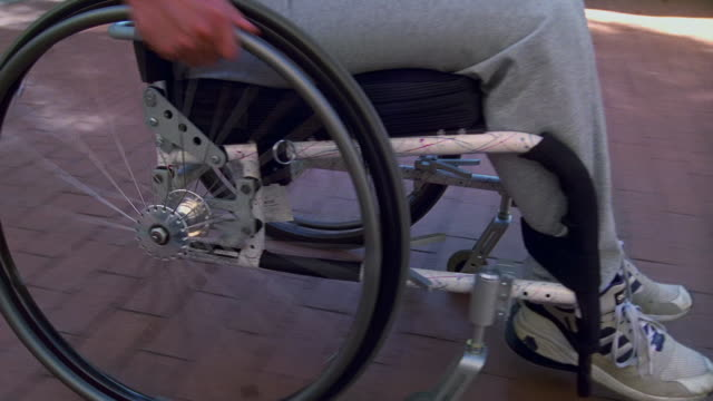 close up dolly shot man's arm pushing wheel on wheelchair / tucson, arizona - wheelchair stock videos & royalty-free footage
