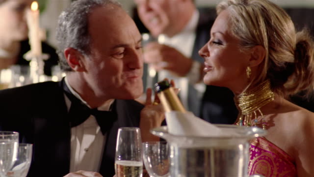 close up dolly shot mature wealthy couple drinking champagne / man giving surprised woman ring - formalwear stock videos & royalty-free footage