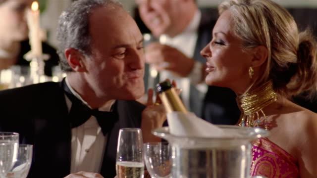 close up dolly shot mature wealthy couple drinking champagne / man giving surprised woman ring - formell klädsel bildbanksvideor och videomaterial från bakom kulisserna