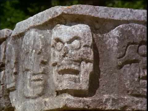 close up dolly shot of stone carvings of skulls / chichen itza, yucatan, mexico - 古代の遺物点の映像素材/bロール