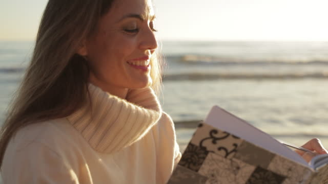 Close up dolly shot of woman reading book at the beach/Marbella region, Spain