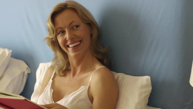 close up dolly shot of woman reading in bed/marbella region, spain - 40 44 years stock videos & royalty-free footage