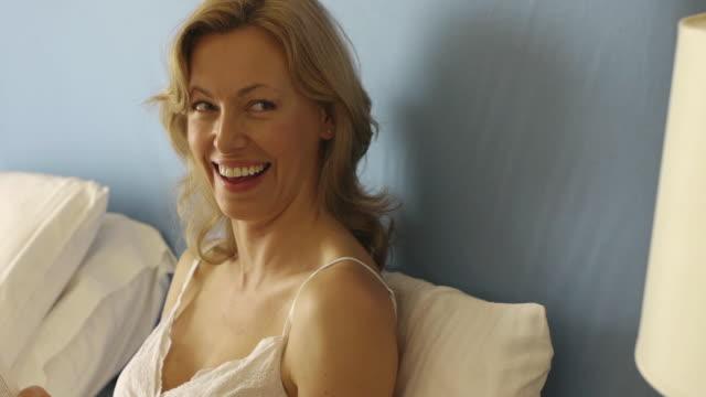 vídeos de stock, filmes e b-roll de close up dolly shot of woman reading in bed/marbella region, spain - 40 44 anos