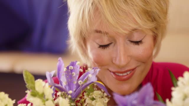 vídeos de stock e filmes b-roll de close up dolly shot of woman smelling flower scent. - 50 54 anos
