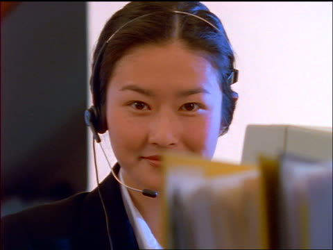 close up dolly shot PORTRAIT Asian woman operator wearing headset + smiling at camera