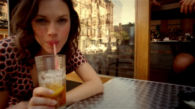 Close up dolly shot portrait of woman drinking iced tea at outdoor table at cafe / Lower East Side, New York City