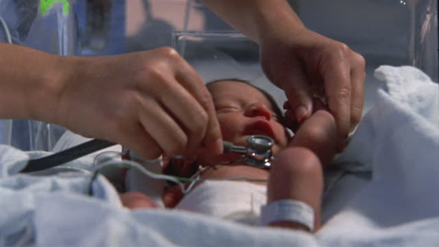 Close up dolly shot premature baby having his heart checked by nurse's stethoscope