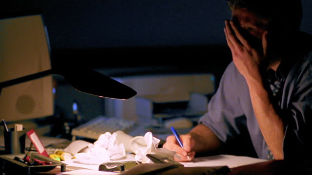 vidéos et rushes de close up dolly shot tired businessman working at desk covered in crumpled papers - crouler sous le travail