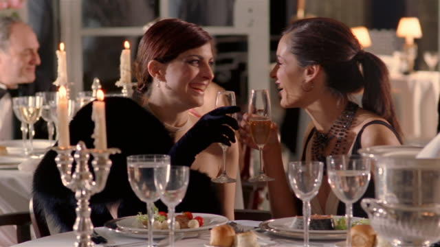 close up dolly shot two women gossiping and toasting with champagne at fancy restaurant - elegance stock videos & royalty-free footage