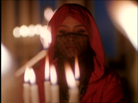 close up dolly shot veiled Middle Eastern woman lighting candles / Morocco
