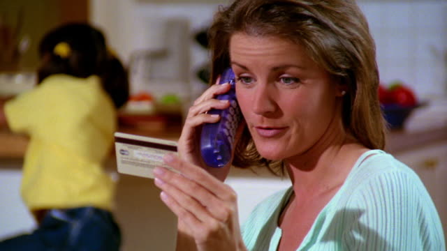 close up dolly shot pan woman talking on phone with credit card in hand / children in background - コードレスフォン点の映像素材/bロール