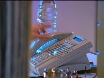 vídeos y material grabado en eventos de stock de close up dolly shot woman's hand picking up telephone in office + dialing - teléfono con cable
