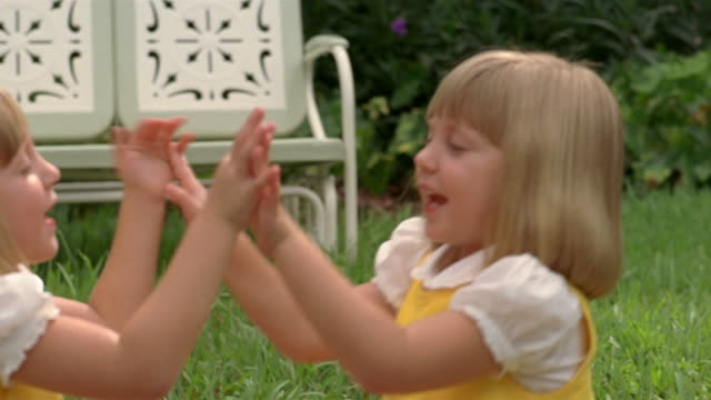 stockvideo's en b-roll-footage met close up dolly shot young twin girls wearing matching outfits sitting on grass and playing pattycake / miami - zus