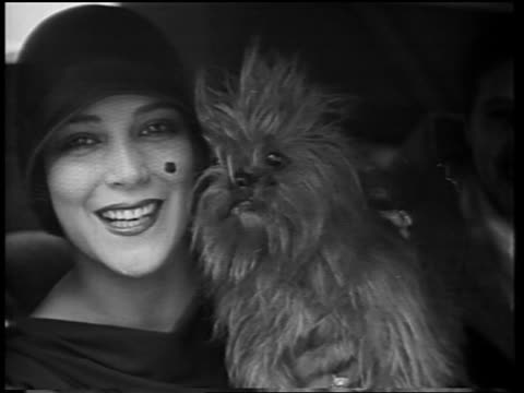 vídeos y material grabado en eventos de stock de close up dolores del rio sitting with dog in car + smiling to camera / newsreel - 1928