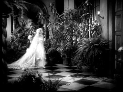 1928 B/W Close up door opening/  Wide shot two men walking in to talk to bride