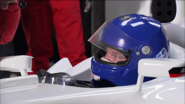 Close up driver sitting behind wheel of Formula One race car / pit boss kneeling down and talking to him