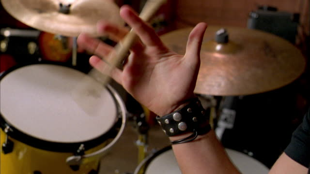 vídeos de stock e filmes b-roll de close up drummer twirling drum stick in fingers w/drums and cymbals in background - rocking