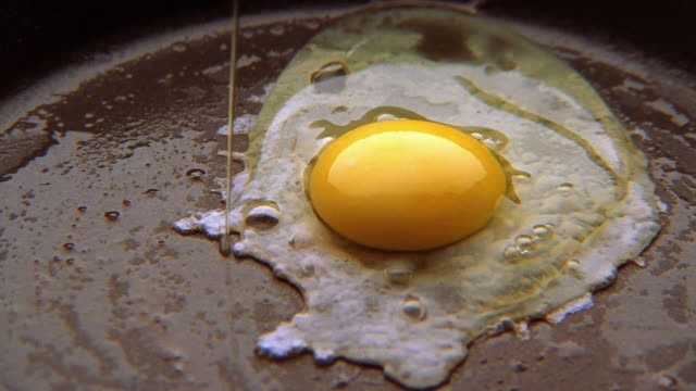 close up egg dropping in frying pan and cooking - egg stock videos & royalty-free footage