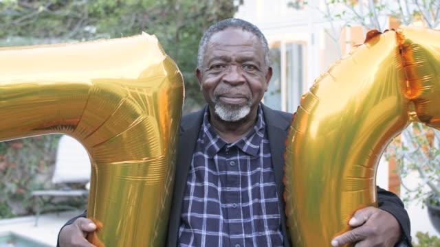 stockvideo's en b-roll-footage met close up, elderly african american man holds birthday balloons - 70 79 jaar