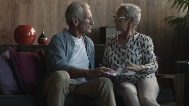 vidéos et rushes de close up, elderly man and woman look at paperwork - retraite