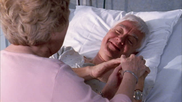 Close up elderly woman talking to elderly man in hospital bed / couple holding hands and smiling