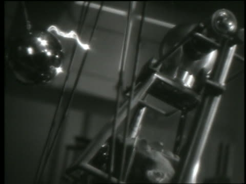 B/W close up electric currents flowing from wires to machines in laboratory experiment